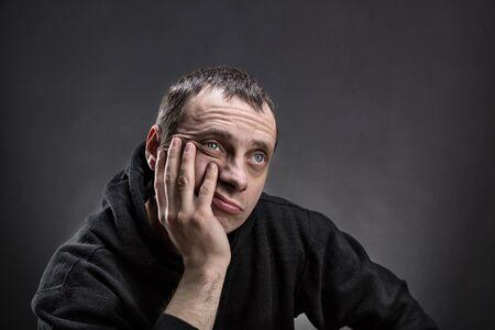 hombre pensando: Hombre pensativo con la palma en su mejilla piensa sobre gris