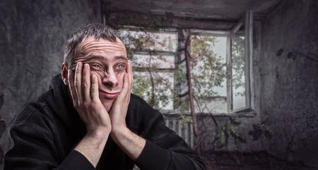 caras tristes: Hombre deprimido con las palmas en sus mejillas piensa en un apartamento viejo gueto