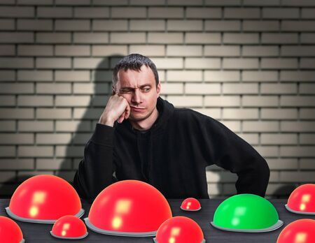 Thinking man chooses right button over brick wall photo