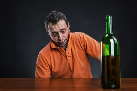 borracho: Hombre borracho mira la botella de alcohol