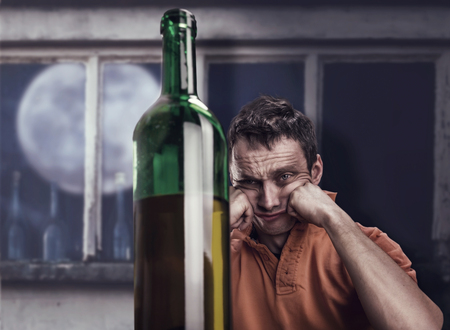 hangover: Drunk man looks at the bottle of wine at night Stock Photo