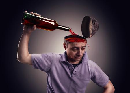 Man déverse son tête avec de l'alcool au cours de gris