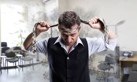 Agressive businessman fighter with a tie on his head in the office Stock Photo