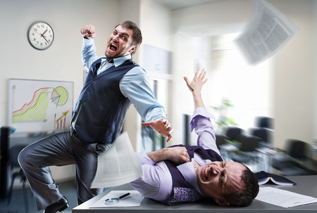 Two agressive businessmen fighting in the office Stock Photo