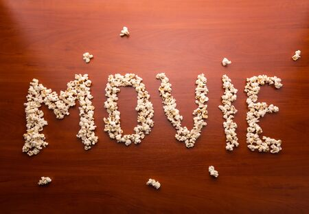 fresh pop corn: Popcorn forming the word movie on the wooden table