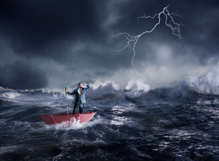 storm sea: Businessman in the umbrella sails in storm in the night