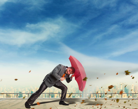 whirlwind: Businessman protects himself from rocks with umbrella