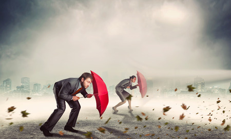 Businessman and businesswoman protect themselves from rocks with umbrella in storm
