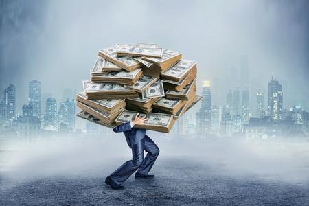 Businessman carrying huge heap of money