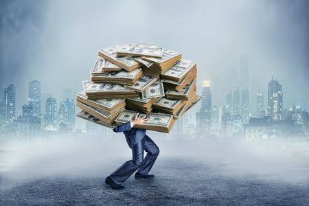 man holding money: Businessman carrying huge heap of money