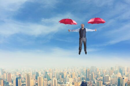 Businessman flying with two red umbrellas photo