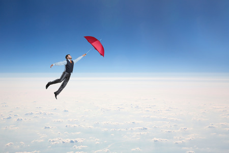 Man flying in the sky with red umbrella in his hand photo