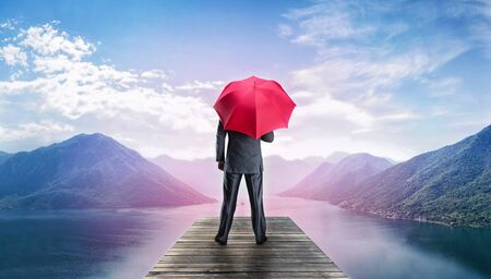 Man with red umbrella standing back on the pier in mountains in the morning photo