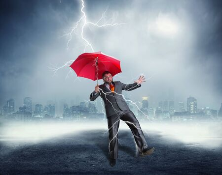 Businessman with the umbrella is struck by lightning