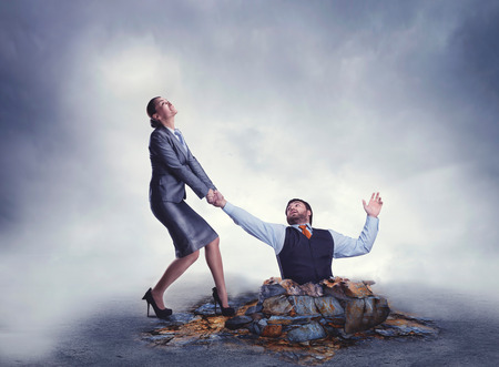 get out: Businesswoman helps businessman to get out of the trap Stock Photo