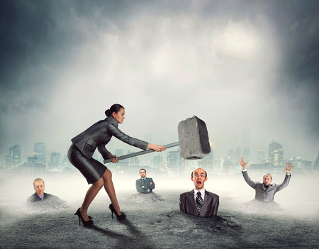 Businesswoman with sledgehammer banging the workers into the ground Stock Photo