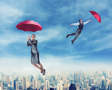 flying man: Dreamy people flying in the sky with red umbrellas in their hands Stock Photo