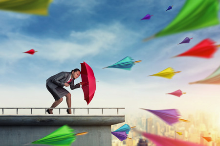 financial freedom: Businesswoman protects herself from problems with umbrella Stock Photo