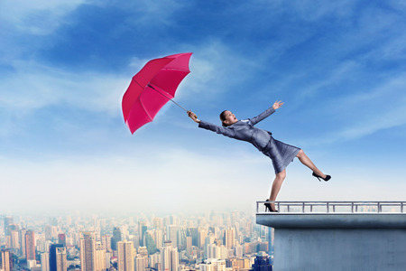 Scared businessoman with umbrella is falling from the edge of the building by wind blow photo