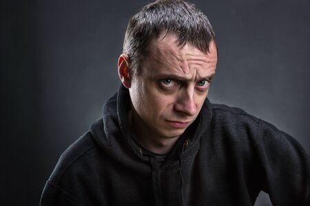 frowning: Closeup of an adult frowning man over grey