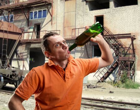 alcoholic man: Man is drinking alcohol in slums