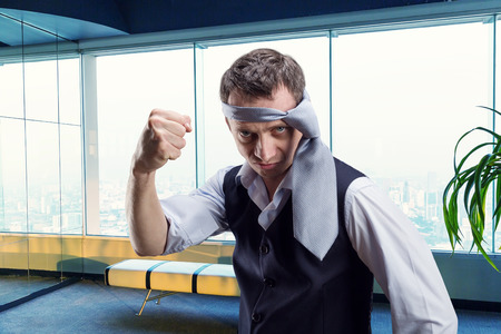 spite: Angry businessman with a tie on his head in the office