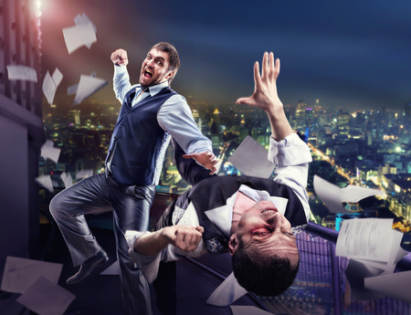 fist fight: Two businessmen fighting on the roof against night cityscape Stock Photo