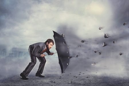 Business man protects himself from rocks with umbrella over grey