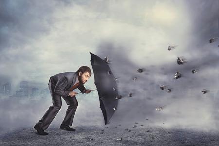 Business man beschermt zich van rotsen met paraplu over grijze Stockfoto