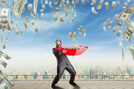lluvia paraguas: Hombre de negocios con paraguas llenos de dinero y el dinero están cayendo