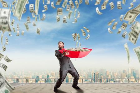 uomo sotto la pioggia: Uomo d'affari con ombrello piene di denaro e il denaro sono in calo