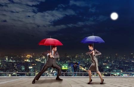 falta de respeto: Los hombres de negocios est�n luchando con los paraguas en la noche Foto de archivo