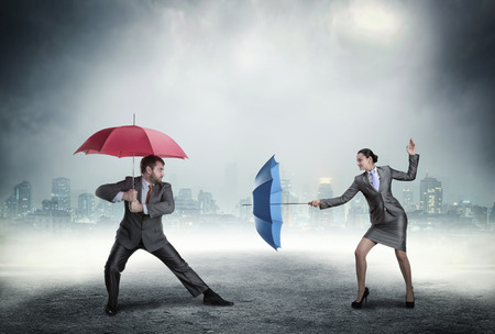 disrespect: Business people fighting with umbrellas against cityscape in the night Stock Photo