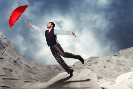 flying man: Man flying with red umbrella in his hand over papers Stock Photo