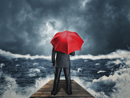 Man with red umbrella standing back on the pier at night storm