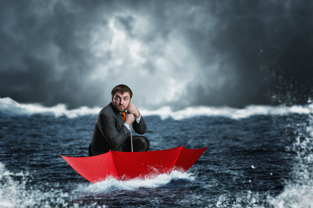 Scared businessman in the umbrella sails in the sea in the night Banque d'images