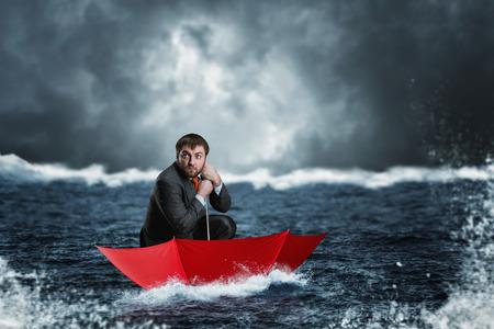 Scared businessman in the umbrella sails in the sea in the night Stock Photo