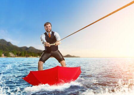 Happy businessman on water surfing in red umbrella