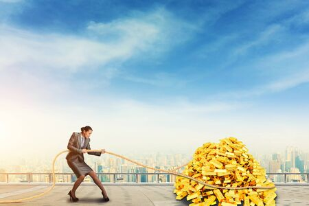 gold bars: Businesswoman pulls the pile of gold bars against blue sky Stock Photo