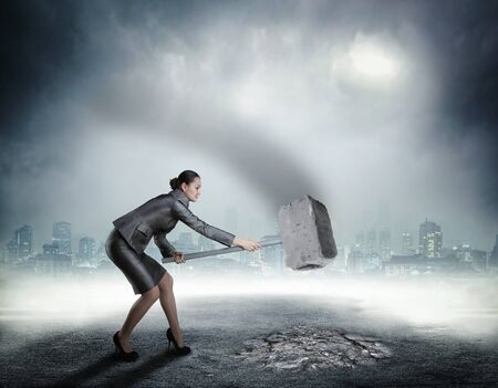 banging: Businesswoman with sledgehammer banging the ground Stock Photo