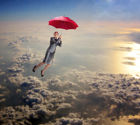 Dreamy woman flying in the sky with red umbrella in her hands photo