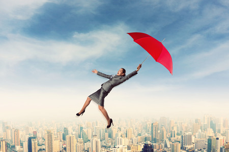 Scared woman flying in the sky with red umbrella in her hand photo