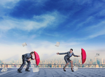 Businessman and businesswoman with red umbrellas on the roof in storm Stock Photo - 39184388