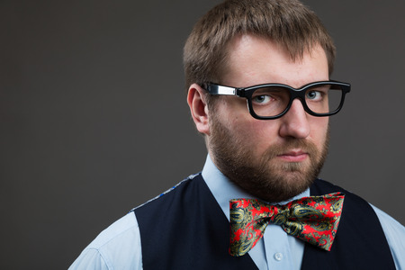 Suspicious man in glasses looks at you over grey background photo