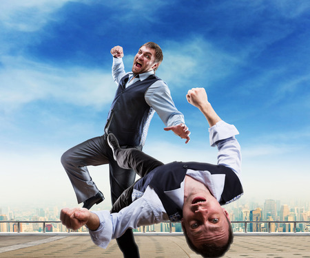 Two businessmen fighting on the roof Stock Photo