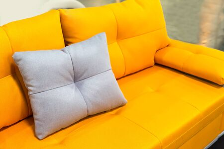 white pillow: Yellow sofa with white pillow