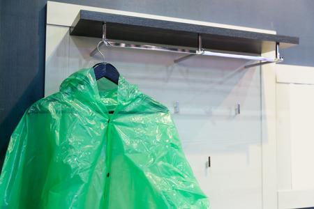 mackintosh: Green raincoat hangs on the rack
