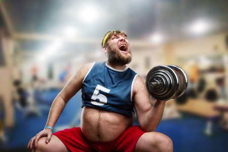 Fat man do hard exercises with a dumbbell in the gym