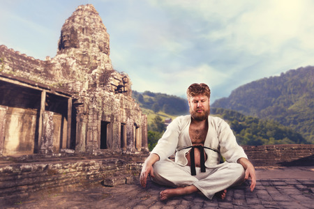 black belt: Fat karate fighter sits with crossed legs meditating