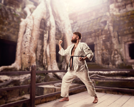 kata: Fat bearded karate fighter in white kimono doing kata against temple